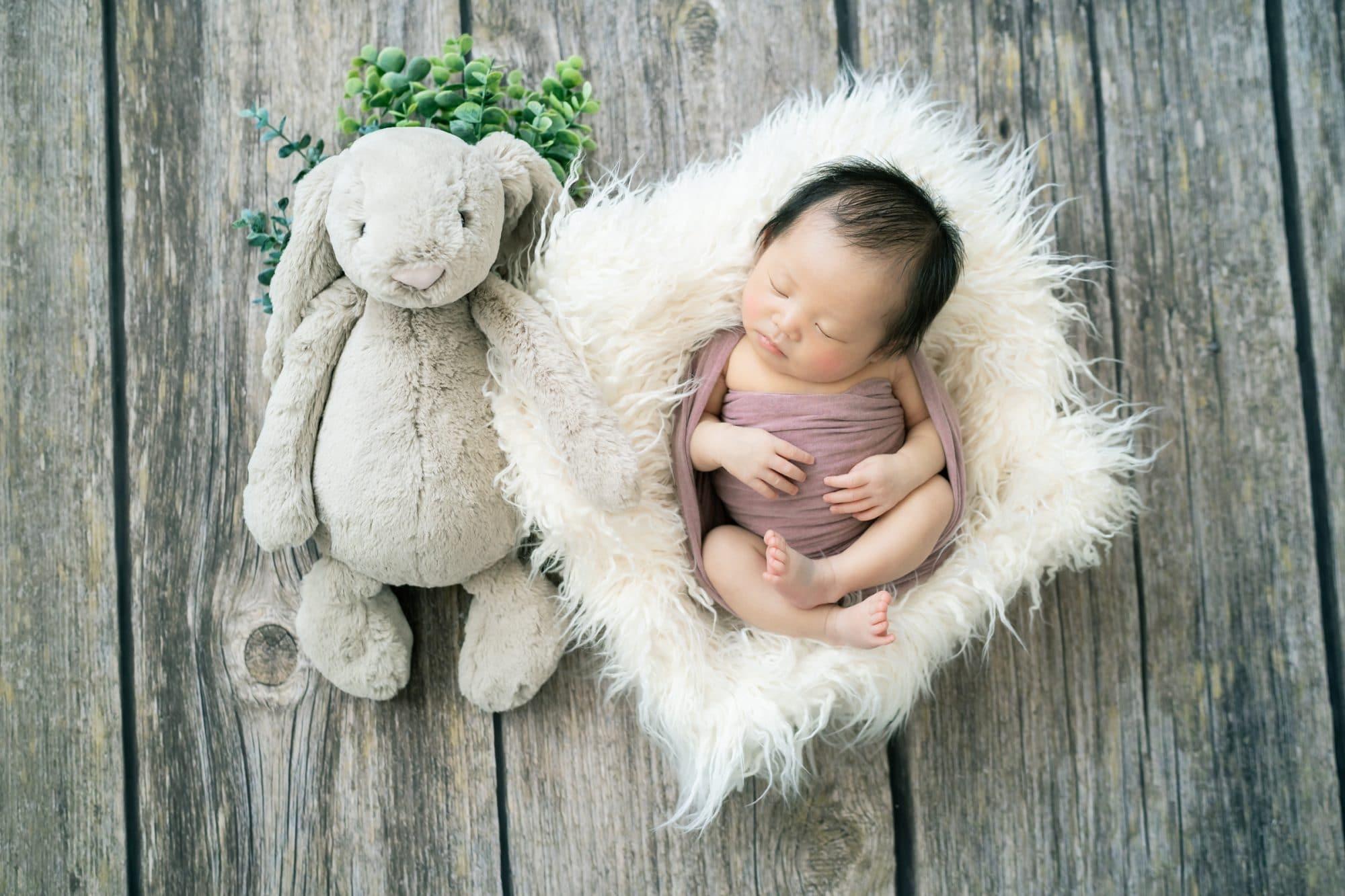 ウサギのぬいぐるみと一緒に箱に入って布に巻かれた赤ちゃん