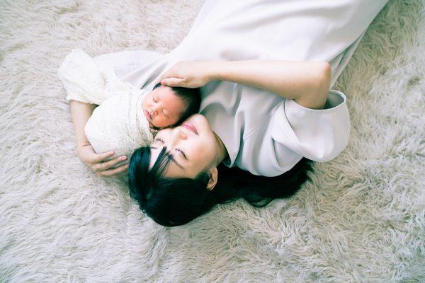敷物にねころぶロングヘアーのお母さんと赤ちゃん