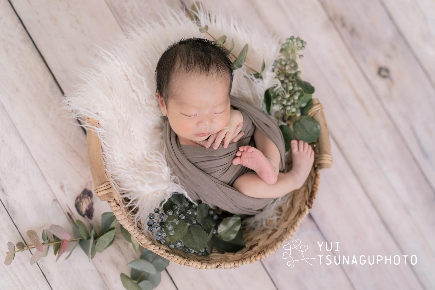 かごの中でふわふわの敷物にくるまって眠る赤ちゃん